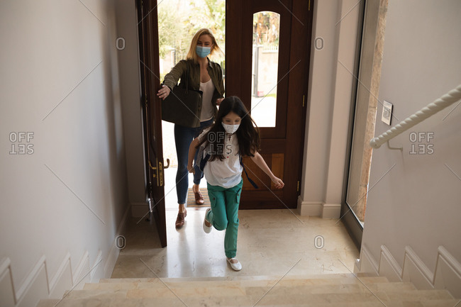 Caucasian woman and her daughter entering house, wearing face masks, opening door. Social distancing during Covid 19 Coronavirus quarantine lockdown.