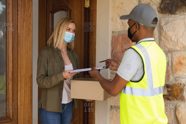 Caucasian woman spending time at home, wearing face mask, receiving a package from delivery man. Social distancing during Covid 19 Coronavirus quarantine lockdown.