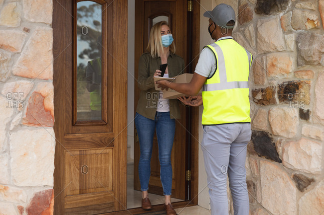 Caucasian woman spending time at home, wearing face mask, receiving a package from delivery man and paying by smartphone. Social distancing during Covid 19 Coronavirus quarantine lockdown.