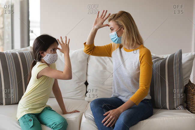 Caucasian woman and her daughter spending time at home together, wearing face masks, having a conversation using sign language. Social distancing during Covid 19 Coronavirus quarantine lockdown.