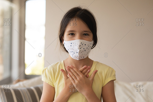 Portrait of Caucasian girl spending time at home, wearing face mask, looking at camera, using sign language. Social distancing during Covid 19 Coronavirus quarantine lockdown.