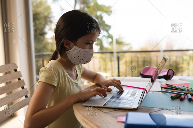 Caucasian girl spending time at home, wearing face mask, using a laptop computer during online school lesson. Social distancing during Covid 19 Coronavirus quarantine lockdown.