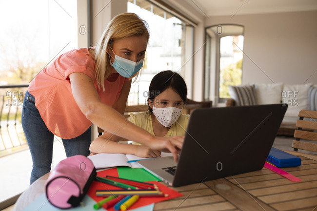 Caucasian woman and her daughter spending time at home, wearing face masks, using a laptop computer during online school lesson. Social distancing during Covid 19 Coronavirus quarantine lockdown.