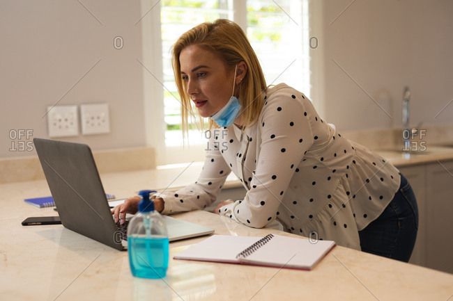 Caucasian woman working from home, wearing face mask, using laptop computer. Social distancing during Covid 19 Coronavirus quarantine lockdown.