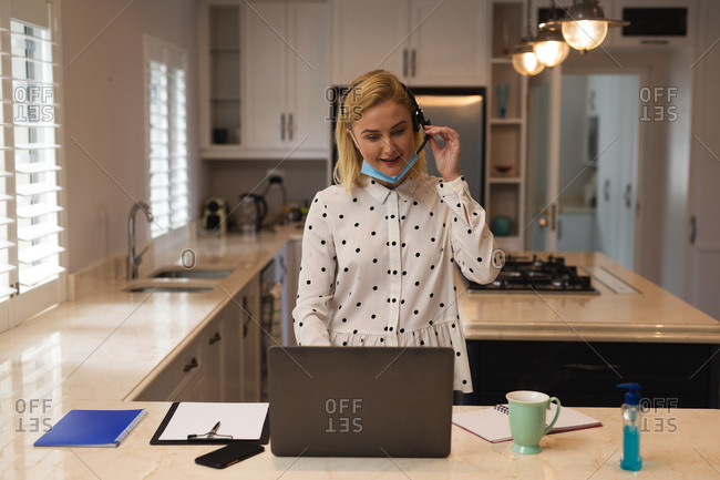 Caucasian woman working from home, wearing face mask, wearing headset and using laptop computer. Social distancing during Covid 19 Coronavirus quarantine lockdown.