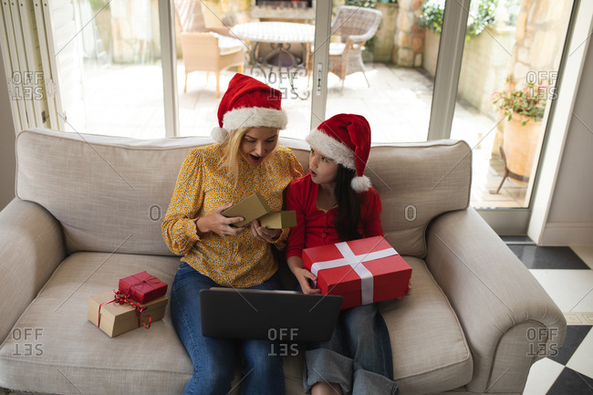 Caucasian woman and her daughter spending time at home together, wearing santa hats, using a laptop computer, making a video call. Social distancing during Covid 19 Coronavirus quarantine lockdown.