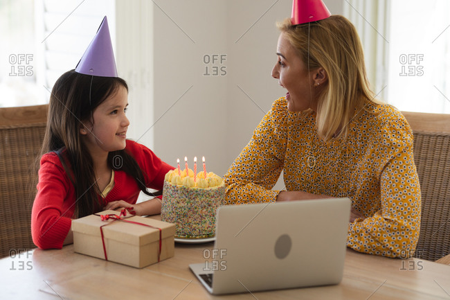 Caucasian woman and her daughter spending time at home together, celebrating birthday, using a laptop computer, making a video call. Social distancing during Covid 19 Coronavirus quarantine lockdown.