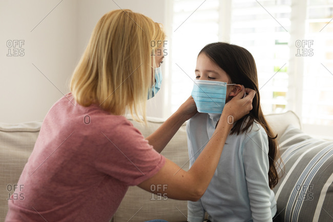 Caucasian woman and her daughter spending time at home together, mother helping daughter put face mask on. Social distancing during Covid 19 Coronavirus quarantine lockdown.