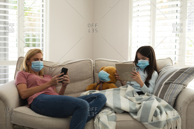 Caucasian woman and her daughter spending time at home together, wearing face masks, sitting on a sofa, using smartphone and tablet. Social distancing during Covid 19 Coronavirus quarantine lockdown.