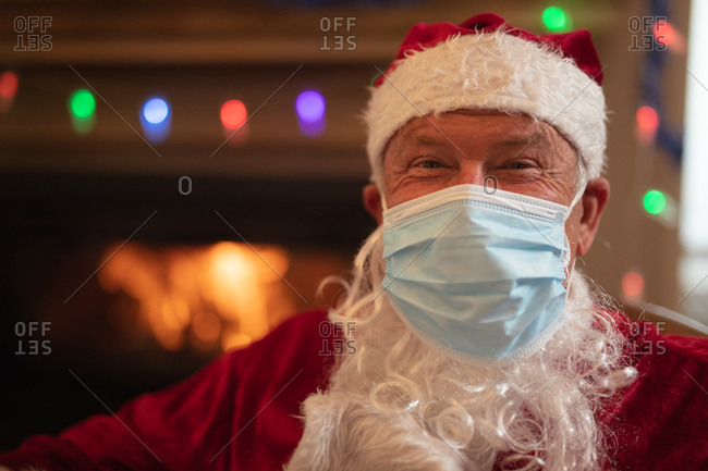 Portrait of senior Caucasian man at home dressed as Father Christmas, wearing face mask, looking at camera. Social distancing during Covid 19 Coronavirus quarantine lockdown.