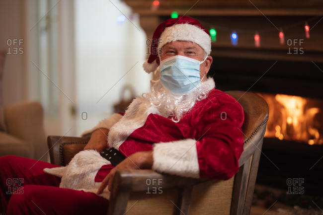 Senior Caucasian man at home dressed as Father Christmas, wearing face mask, sitting on a chair by fireplace. Social distancing during Covid 19 Coronavirus quarantine lockdown.