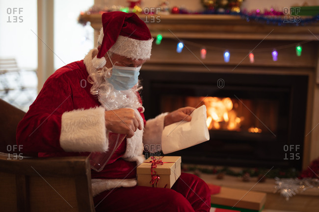 Senior Caucasian man at home dressed as Father Christmas, wearing face mask, disinfecting a present. Social distancing during Covid 19 Coronavirus quarantine lockdown.