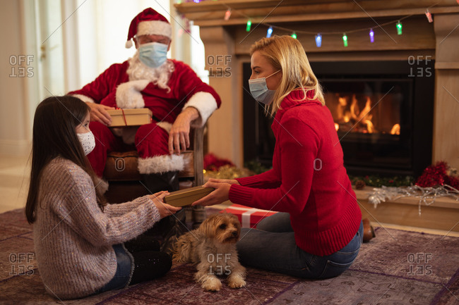 Senior Caucasian man, his adult daughter and granddaughter at home dressed as Father Christmas, wearing face mask, giving presents. Social distancing during Covid 19 Coronavirus quarantine lockdown.