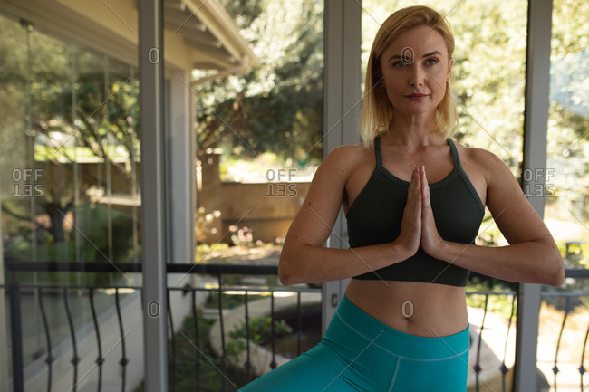 Caucasian woman spending time at home, doing yoga, meditating. Social distancing during Covid 19 Coronavirus quarantine lockdown.