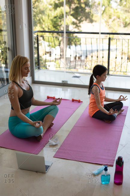 Caucasian woman and her daughter spending time at home together, doing yoga, meditating. Social distancing during Covid 19 Coronavirus quarantine lockdown.