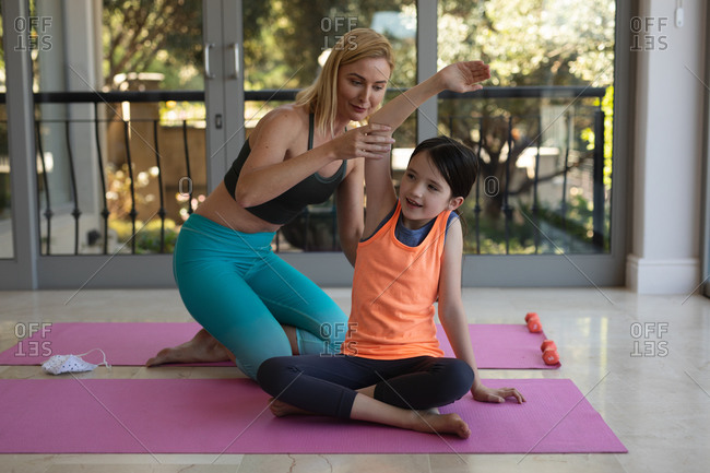 Caucasian woman and her daughter spending time at home together, doing yoga, stretching. Social distancing during Covid 19 Coronavirus quarantine lockdown.