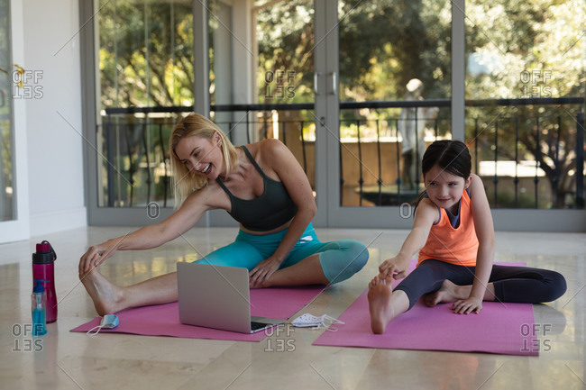 Caucasian woman and her daughter spending time at home together, doing yoga, stretching, using laptop computer. Social distancing during Covid 19 Coronavirus quarantine lockdown.