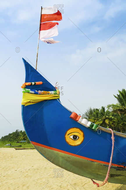 October 15, 2017: Colorful fishing boat with Indian flag and golden eye motifs on Marari Beach, Mararikulam, Alappuzha (Alleppey), Kerala, India, Asia