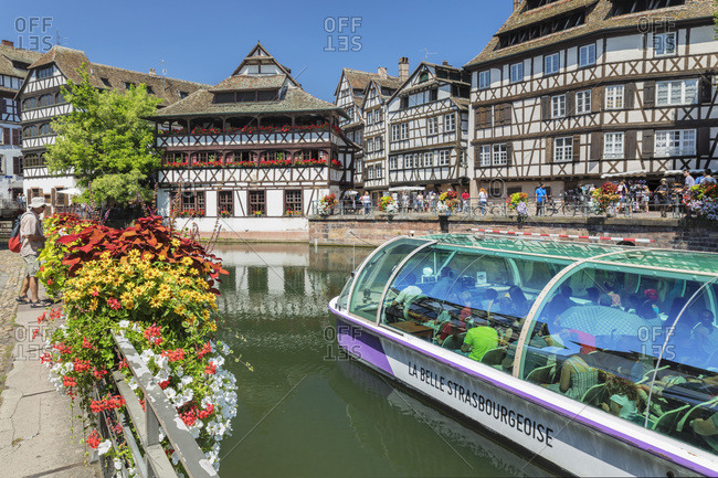 July 19, 2018: Excursion boat on River Ill, Maison des Tanneurs, La Petite France, UNESCO World Heritage Site, Strasbourg, Alsace, France, Europe