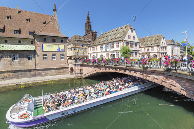 July 19, 2018: Excursion boat on River Ill, Historical Museum and Cathedral, Strasbourg, Alsace, France, Europe