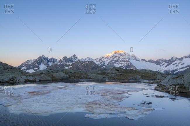 Sunrise over the snowy peak of Monte Disgrazia, Alpe Fora, Valmalenco, Sondrio province, Valtellina, Lombardy, Italy, Europe