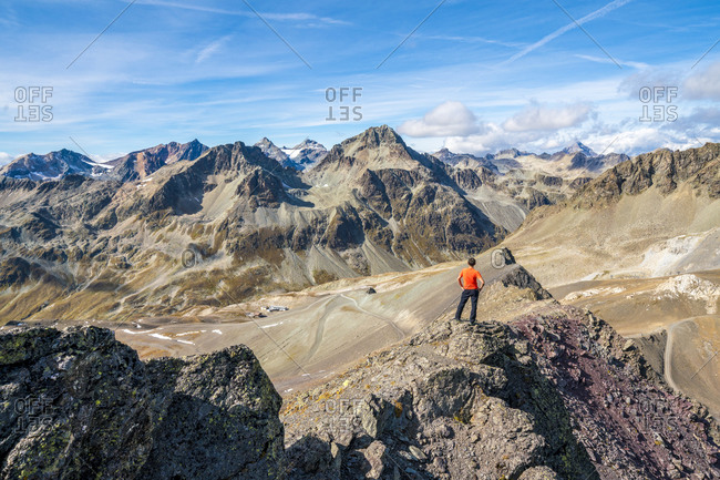 Rear view of man on top of Piz Nair looking towards Piz Suvretta mountain peak, Engadine, canton of Graubunden, Switzerland, Europe