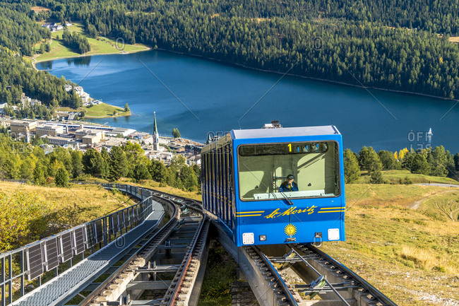 September 30, 2019: Funicular car uphill with St. Moritz lake and village in the background, Engadine, canton of Graubunden, Switzerland, Europe