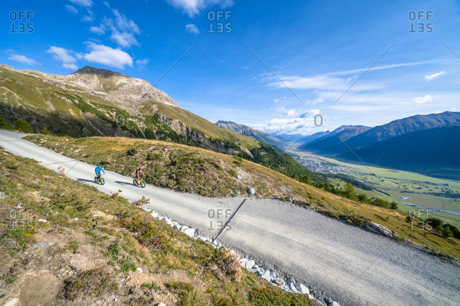 Elevated view of tourists riding downhill scooters on mountain path, Celerina, Engadine, canton of Graubunden, Switzerland, Europe