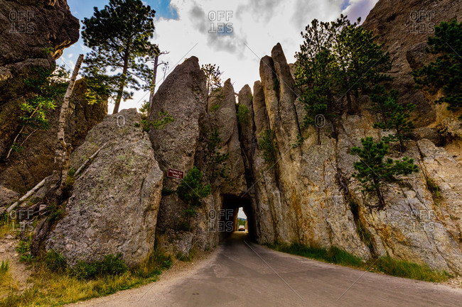 Tiny road passing under a small mountain in the Black Hills of Keystone, South Dakota, United States of America, North America