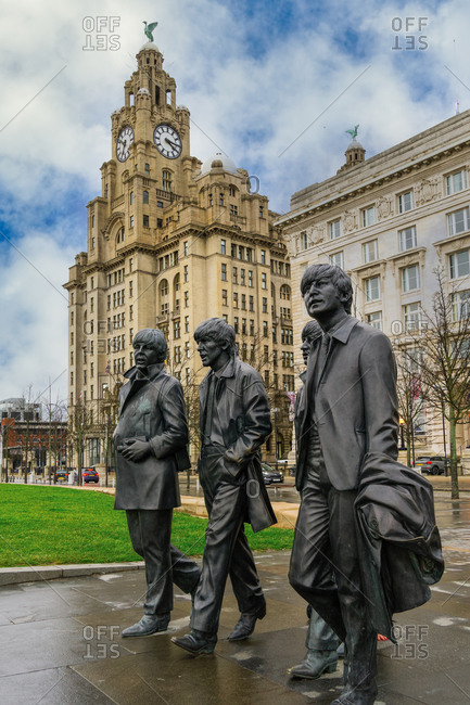 February 21, 2020: The Beatles statue, bronze art depicting the famous band facing river Mersey with Royal Liver Building in the background, Liverpool, Merseyside, England, United Kingdom, Europe