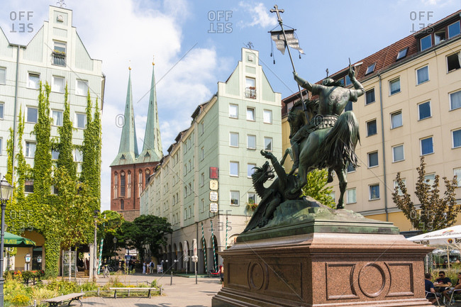 August 28, 2019: Nikolaiviertel (Nicholas Quarter) at sunset near Alexander Platz with statue of St. George Slaying The Dragon and church spires, Berlin, Germany, Europe