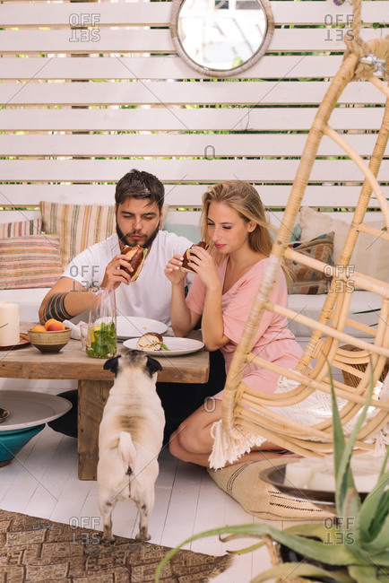 Young couple having breakfast at home while their dog is watching them