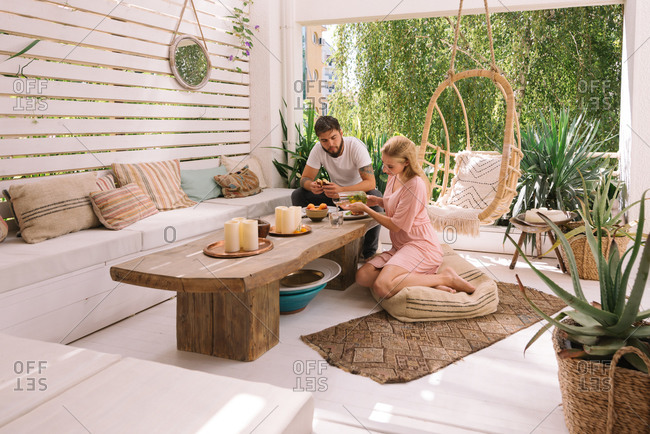 Couple having breakfast at their home on a beautiful boho terrace