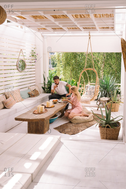 Young adult couple having breakfast at their home on a beautiful boho terrace