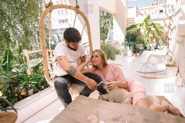 Couple spending time on their beautiful boho balcony with their small dog