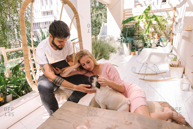 Young couple spending time on their beautiful boho balcony with their small dog