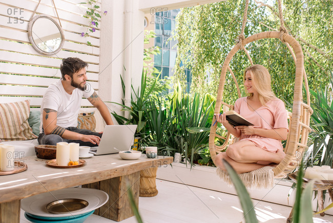 Couple working from home during quarantine on their terrace
