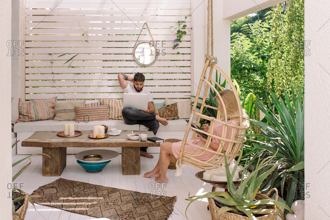 Couple working from home in boho apartment during quarantine