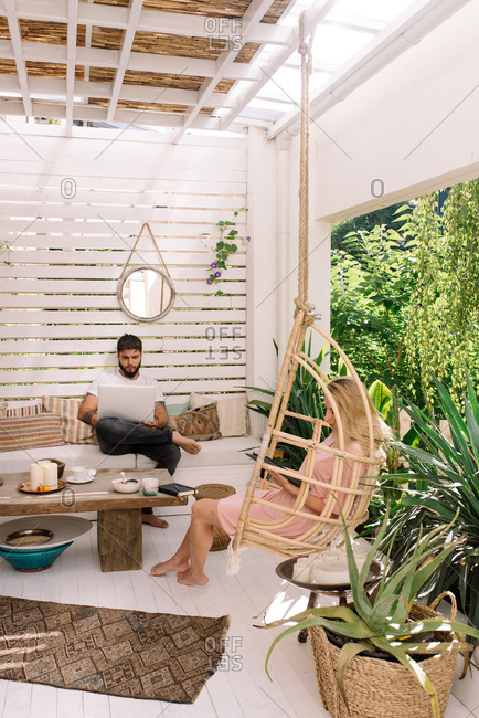 Young couple working from home in boho apartment during quarantine
