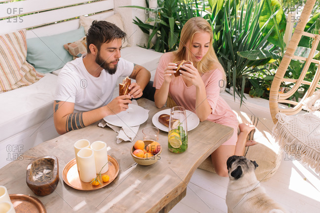 Couple having breakfast at home while their dog is watching them