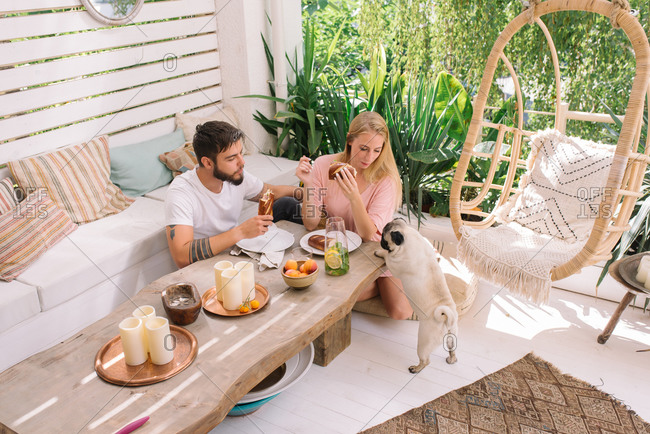 Young couple having breakfast in their beautiful boho style apartment