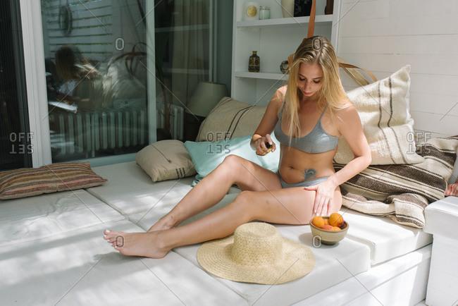 Beautiful woman applying sun tan spray on her terrace at home