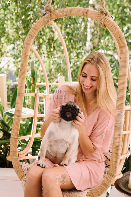 Blonde woman petting her pug while sitting in a hanging chair outdoors