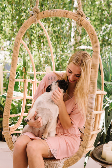 Blonde woman holding her pet pug in her lap