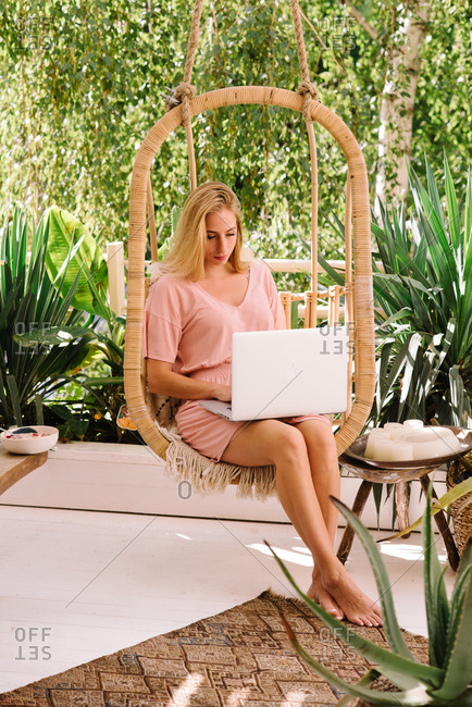 Woman sitting in a hanging chair on terrace working on laptop
