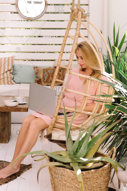 Young woman sitting on terrace working on laptop computer