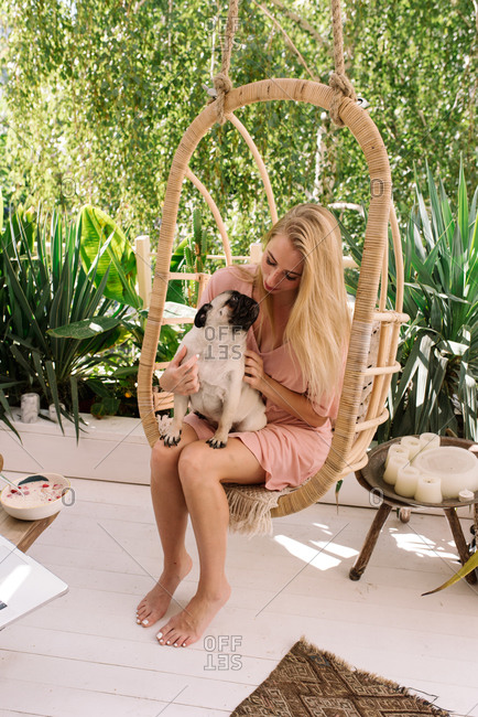 Blonde woman snuggling with her pet pug in a hanging chair