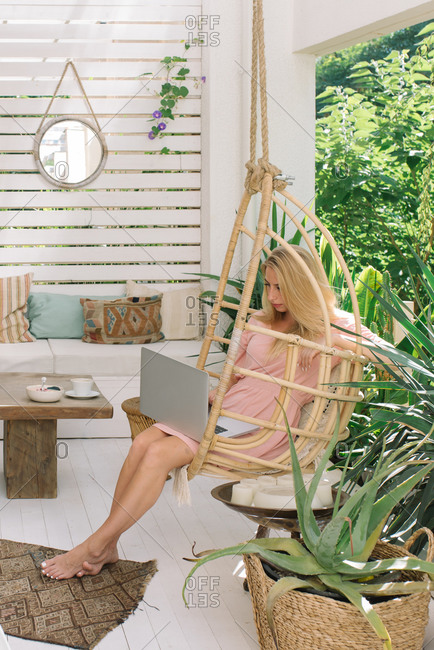 Young woman sitting on terrace at home working on laptop computer