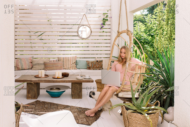 Beautiful woman working from home on her beautiful boho terrace