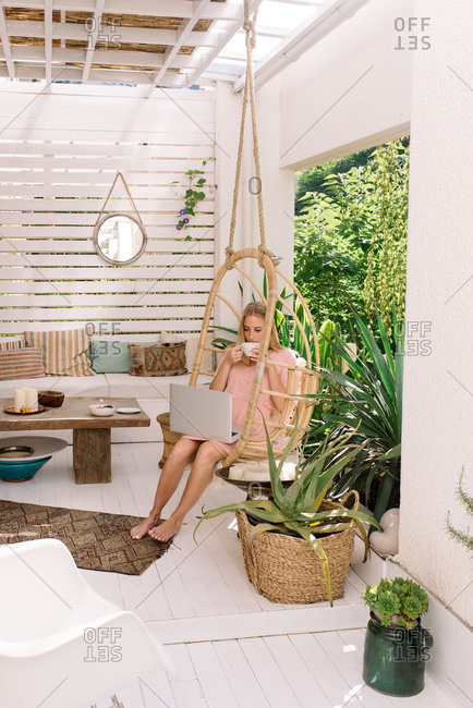 Beautiful woman working from home on her beautiful boho terrace and drinking coffee